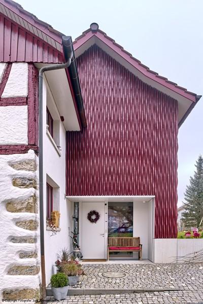 Die wohnräume im ehemaligen überhohen heutenn sind neu ringförmig um den mittig gesetzten kachelofen angeordnet